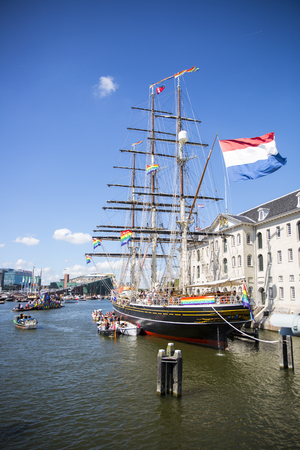 transexual: Amsterdam, the Netherlands - August 06, 2016: 3 mast sailboat Clipper Stad Amsterdam in front od the Maritime Museum Scheepvaartmuseum, participating in annual event Gay Pride Parade, Euro Pride 2016 Editorial