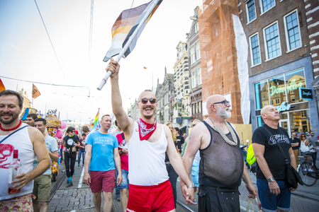 transexual: Amsterdam, the Netherlands - July 23, 2016: Gay couple holding hands at Pride Walk, demonstration parade from Vondelpark to Dam Square during Pink Saturday Gay Euro Pride celebrations