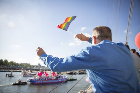 rainbow flag: Man waving a rainbow flag during the annual event Gay Pride Parade, Euro Pride 2016, August 6
