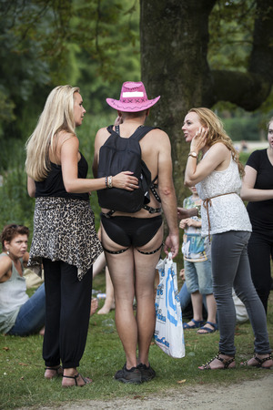 Amsterdam, the Netherlands – July 23, 2016:  Gay man in inderwear surrounded by 2 female friends in the Vondelpark for Pink Saturday 2016 Gay Euro Pride celebrations