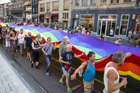 identidad cultural: Amsterdam, Holanda - 23 de julio 2016: El orgullo Walk, Raimbow bandera de difusión y en poder de las personas durante el desfile de la demostración de Vondelpark de la plaza Dam durante las celebraciones del Sábado rosa Gay Europride Editorial