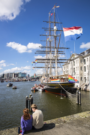 Amsterdam, the Netherlands - August 06, 2016: 3 mast sailboat Clipper Stad Amsterdam in front od the Maritime Museum Scheepvaartmuseum, participating in annual event Gay Pride Parade, Euro Pride 2016 Editorial