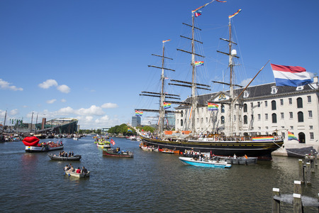 identidad cultural: Amsterdam, the Netherlands - August 06, 2016: 3 mast sailboat Clipper Stad Amsterdam in front od the Maritime Museum Scheepvaartmuseum, participating in annual event Gay Pride Parade, Euro Pride 2016 Editorial