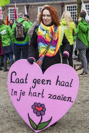 Amsterdam, The Netherlands - February 6,2016: multi-cultural demonstration against the Islamization of Europe with slogan: Refugees welcome, racism is not! A woman is holding a sign sauing Dont let the hate grow in your heart