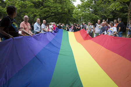 Amsterdam, the Netherlands - July 23, 2016: Pride Walk, Raimbow flag spread and held by people during the demonstration parade from Vondelpark to Dam Square during Pink Saturday Gay Euro Pride celebrations