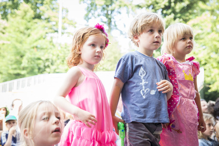 Amsterdam, the Netherlands - July 23, 2016: little children attending to the shows and activities in Vondelpark during Pink Saturday celebrations for the 2016 Gay Euro Pride