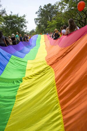 identidad cultural: Amsterdam, the Netherlands - July 23, 2016: Pride Walk, Raimbow flag spread and held by people during the demonstration parade from Vondelpark to Dam Square during Pink Saturday Gay Euro Pride celebrations