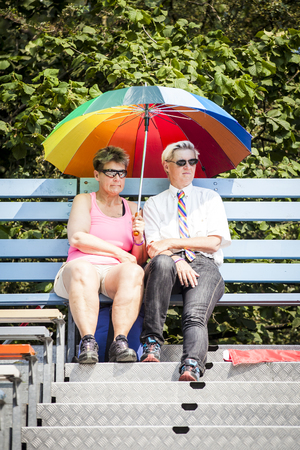 Amsterdam, the Netherlands - July 23, 2016: 2 women protecting themselves form the sun under a rainbow colored umbrella at Pink Saturday celebration in the Vondelpark for 2016 Gay Euro Pride