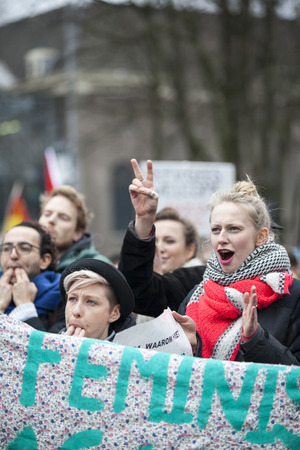 Amsterdam, The Netherlands - February 6,2016: public multi-cultural demonstration organized to protest against racism and islamophobia named Refugees welcome, racism not! Woman holding a sign saying later, you will be the black sheep
