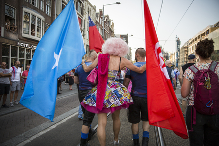 Amsterdam, the Netherlands - July 23, 2016: drag queen surrounded with 2 men holding somalian and turkish flags at Pride walk, demonstration parade from Vondelpark to Dam Square during Pink Saturday Gay Euro Pride celebrations