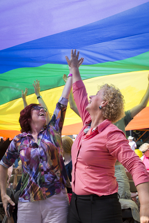 identidad cultural: Amsterdam, the Netherlands - July 23, 2016: public at the Vondelpark open air theater having fun under a rainbow during the Gay EuroPride - Pink Saturday celebrations