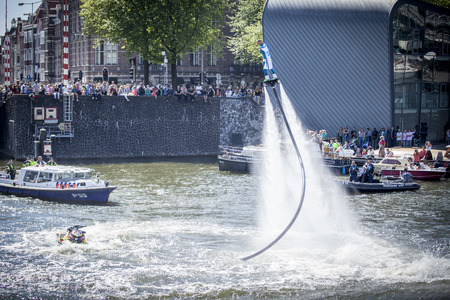 transexual: Amsterdam, the Netherlands - August 06, 2016: man making figures with a flyboard during the annual event for the protection of human rights and civil equality - Gay Pride Parade on the canals during Euro Pride 2016