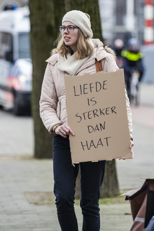 Amsterdam, The Netherlands - February 6,2016: public multi-cultural demonstration organized to protest against racism and islamophobia named Refugees welcome, racism not! A woman holds a sign saying Love is stronger than hate Editorial