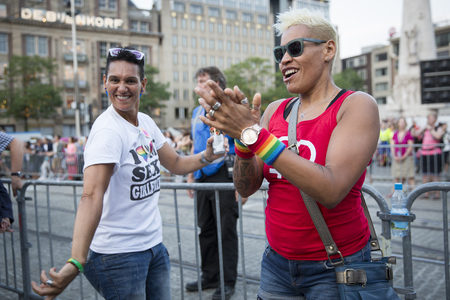 Amsterdam, the Netherlands - July23, 2016: lesbian couple dancing at opening party on Dam square during Pink Saturday celebrations of the Gay EuroPride