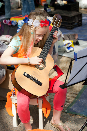 Amsterdam, The Netherlands, April 30, 2014: little girl playing guitar atcelebration of the public national holiday Kings day - Koningsdag - held every year on 30th of April in the entire country to celebrate King Willems birthday