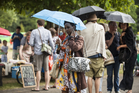 Amsterdam, The Netherlands - July, 5 2015: black woman under umbrella under summer rain during Amsterdam Roots Open Air, a cultural festival held in Park Frankendael on 05072015 Editorial
