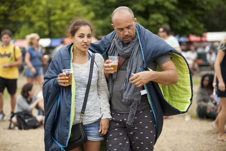 Amsterdam, The Netherlands - July, 5 2015: happy couple wrapped in a sleeping bag sharing a beer  during Amsterdam Roots Open Air, a cultural festival held in Park Frankendael on 05072015 Editorial