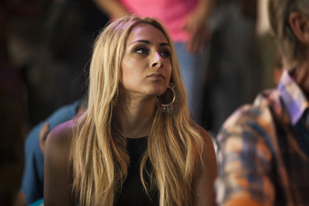Amsterdam, The Netherlands - July, 5 2015: young woman listening to concert of Moroccan band Generation Taragalte, Cultural caravan for peace at Amsterdam Roots Open Air cultural festival held in Park Fraekendael