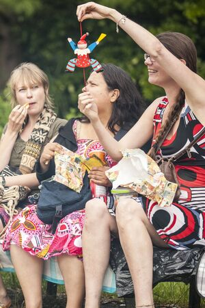 Amsterdam, The Netherlands - July, 5 2015: woman showing a wooden puppet to her friends during Amsterdam Roots Open Air, a cultural festival held in Park Frankendael on 05072015