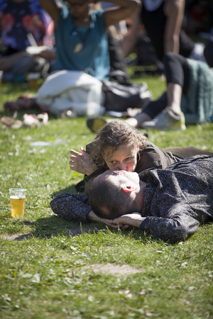 Amsterdam, The Netherlands - July, 3 2016: man and woman couple kissing lying on the grass during Roots Open Air festival