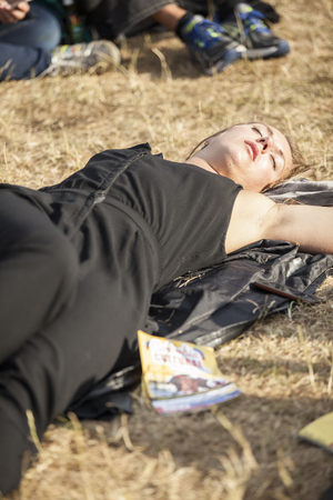 Amsterdam, The Netherlands - July, 5 2015: young woman lying in the grass, sleeping under the sun during Amsterdam Roots Open Air, a cultural festival held in Park Frankendael on 05072015