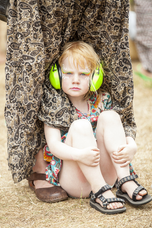 Amsterdam, The Netherlands - July, 5 2015: little girl with make up face sitting on the grass during Amsterdam Roots Open Air, a cultural festival held in Park Frankendael on 05072015