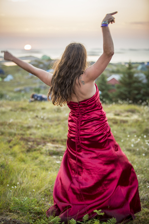 Traena, Norway - July 11 2013: at the Traenafestival, music festival taking place on the small island of Traena, woman in a red silky dress after the concert of Erlend Oye