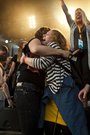johannes: Traena, Norway - July 11 2014: fan huging Ida Maria during the concert of the Norwegian band Ida Maria at the Traenafestival, music festival taking place on the small island of Traena
