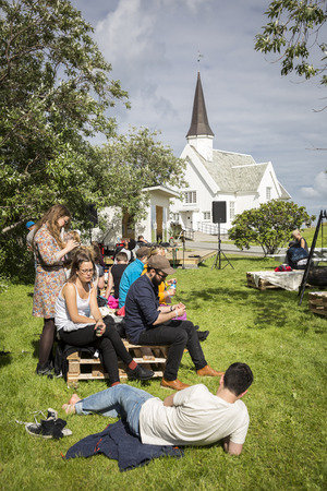Traena, Norway - July 07 2016: people chilling out having a drink during Traenafestival, music festival taking place on the small island of Traena