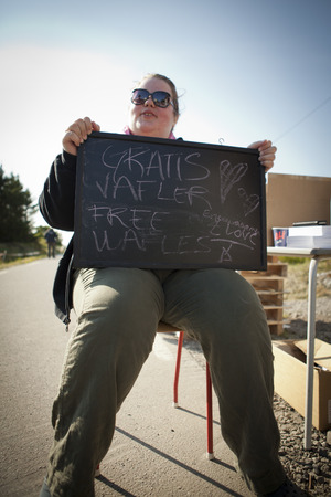 public offering: Traena, Norway - July 10 to 12 2014: at the entrance of the campsite, young woman holding a sign offering free waffles, Traenafestival, music festival taking place on the small island of Traena