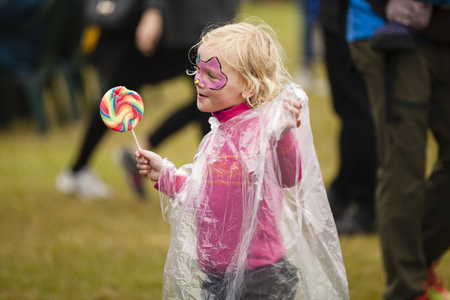 Traena, Norway - July 10 2015: little girl with make up on her face having a rainbow lollipop on the festival field Traenafestival, music festival taking place on the small island of Traena Editorial