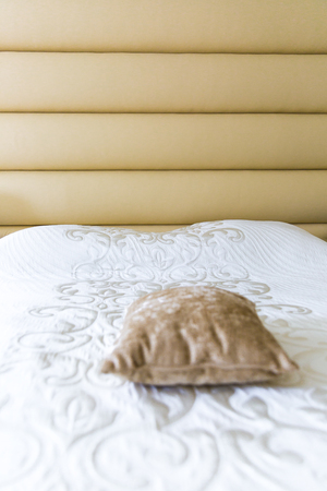 close up on a bed with beige padded headboard and matching cushion and white bedspread