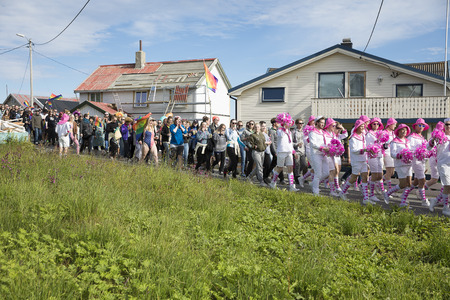 bisexual women: Traena, Norway - July 07 2017: group of colorful people participating in the smallest gay Pride in Europe during Traenafestival, music festival taking place on the small island of Traena.