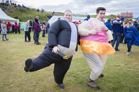 Traena, Norway - July 8 2017: man and woman dressed up as sumo with inflatable suit at Traenafestival, music festival taking place on the small island of Traena