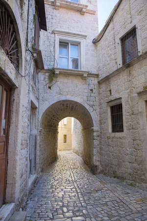 cobblestone street with an arch passage in old town Split, Croatia