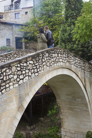 old arch bridge with couple taking a selfie photo in  area of old town Mostar, Bosnia and Herzegovina