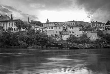 Black and white view of Old Town Mostar from the bank of Neretva River, Bosnia and Herzegovina.