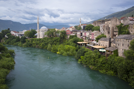 Mostar, Bosnia and Herzegovina - 20 May 2016: Old town, Koski Mehmed Pasa mosque and Neretva River. The old town was destroyed during the Croat-Bosniak war in 1993, reconstructed and now a World Heritage UNESCO site