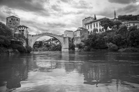 Black and white view of the single-arch Old Bridge or Stari Most crossing the Neretva River in Mostar, Bosnia and Herzegovina. The Old Bridge was destroyed on 9 November 1993 by Croat military forces during the Croat–Bosniak War.