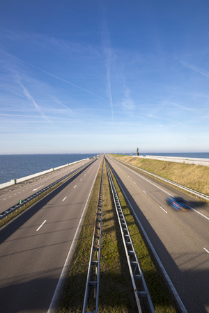Motorway A7 on Afsluitdijk, a dam separating the North Sea from the Ijsselmeer lake. View from bridge at Breezanddijk, an artificial island. Stockfoto - 115873219