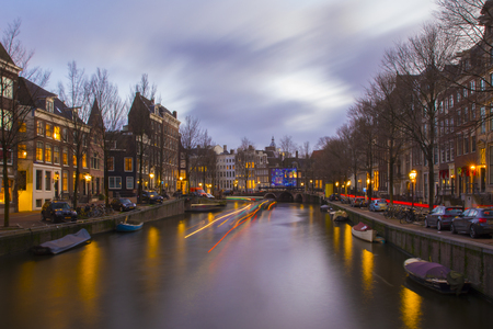 View on romantic canal Keizergracht  in Amsterdam at night with city light and reflection on water Redactioneel
