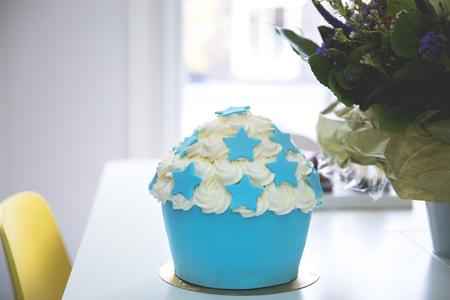Big cupcake wedding or birthday cake  with cream and blue stars frosting decoration