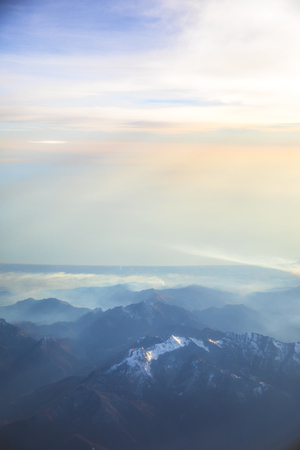 Aerial view over the Mediterranean sea and blue Alps Mountains with soft sunset light