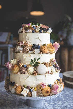 Traditional wedding cake decorated with fruits, biscuits, macaroon and flowers Stockfoto