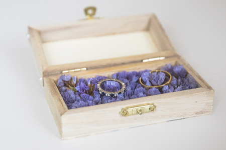 wedding rings in a little wooden box presented on purple flowers Stockfoto