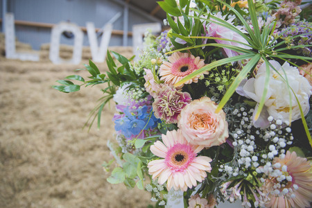 Close up on colorful pastel flower bouquet with LOVE letters in the background