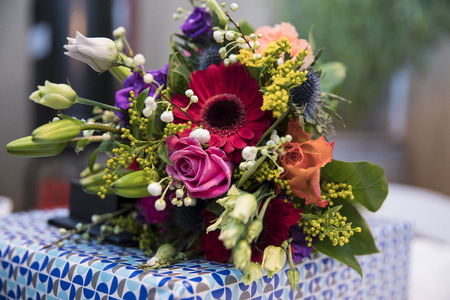 Bouquet of colorful flower lying on a wrapped gift