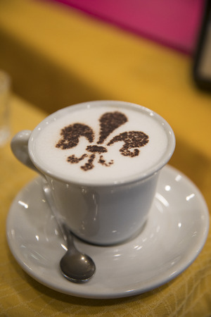Cup of cappuccino coffee with a heraldic lily flower as a decoration