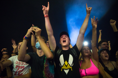 Nyon, Switzerland - 25 July 2019 :  young people in the audien cheering up arms up in the air in front of concert of French rap singer Moha la Squale