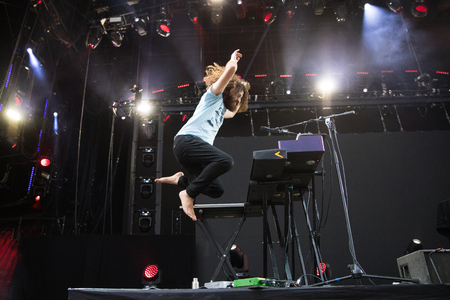 Nyon, Switzerland - 24 July 2019 :  concert of Australian singer-songwriter and multi-instrumentalist Xavier Rudd, pianist is jumping up while playing Editorial